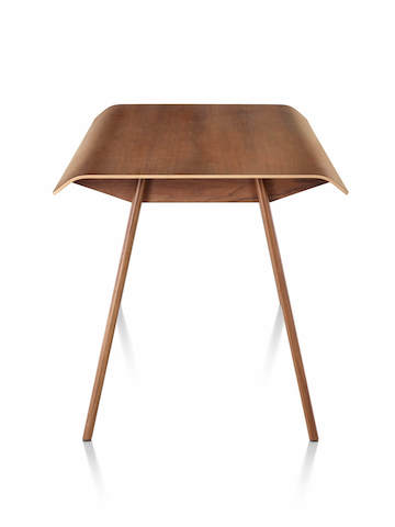 Side view of Herman Miller Distil Table in medium wood tone with molded plywood top and solid wood legs
