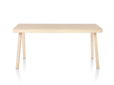 Distil Table from Herman Miller in light wood tone with molded plywood top and solid wood legs, front view.