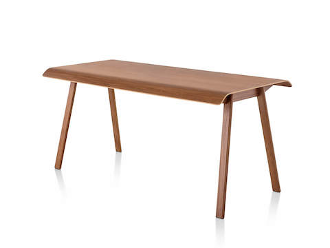 Distil Table from Herman Miller in medium wood tone with molded plywood top and solid wood legs, three quarter view.