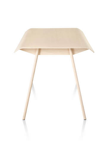 Side view of light wood tone Herman Miller Distil Table with solid wood legs and molded plywood top.