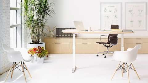Small office with a black Eames Aluminum Group Chair, Renew Sit-to-Stand desk, and two white Eames Molded Plastic Chairs.