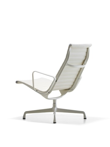 Three-quarter rear view of a white Eames Aluminum Group lounge chair.