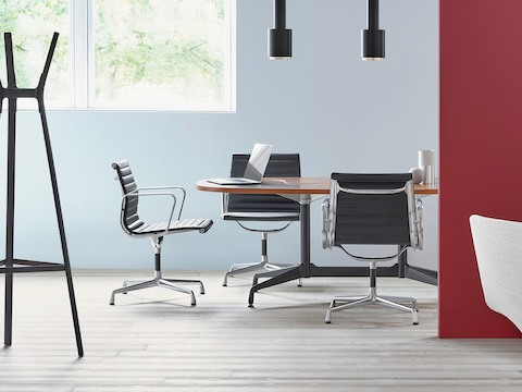 Meeting room with black Eames Aluminum Group mid-back chairs around an Eames Table.