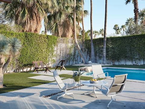 White Eames Aluminum Group outdoor chairs near a swimming pool.