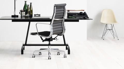 Small office with a black Eames Aluminum Group Chair, black AGL table, and white Eames Molded Fiberglass Chair.