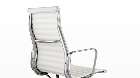 Three-quarter rear view of a white Eames Aluminum Group high-back chair.