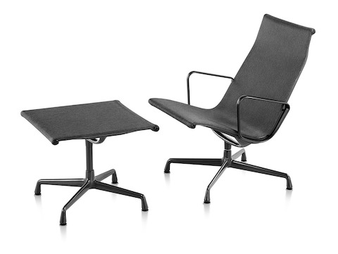 An Eames Aluminum Group outdoor lounge chair and ottoman in a black weave fabric.