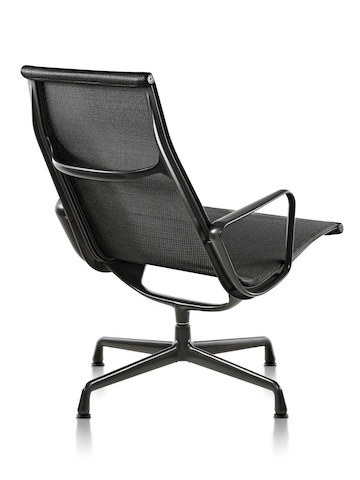 Three-quarter rear view of an Eames Aluminum Group outdoor lounge chair in a black weave fabric.
