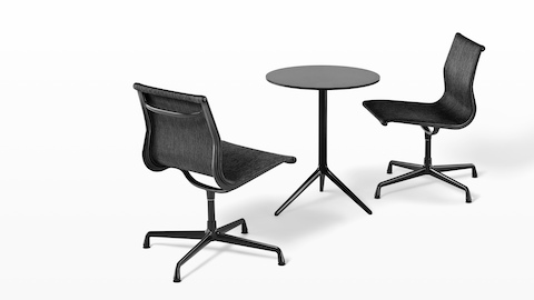 Two armless Eames Aluminum Group outdoor side chairs in a black weave fabric paired with a round black table.