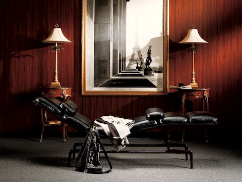 Profile view of a black leather Eames Chaise in a luxurious residential setting.