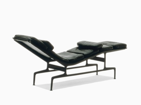 Three-quarter rear view of a black leather Eames Chaise, emphasizing the die-cast aluminum frame.