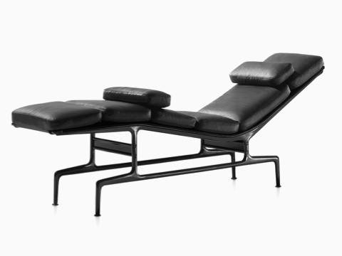 An Eames Chaise with black leather upholstery and a black frame, viewed from a 45-degree angle.