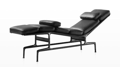 Oblique view of a black leather Eames Chaise with a black frame and two additional loose cushions.