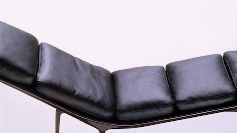 An overhead profile view of a black leather Eames Chaise with an eggplant frame.