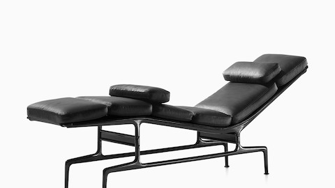 Angled view of a black leather Eames Chaise with a black frame and two additional loose cushions.