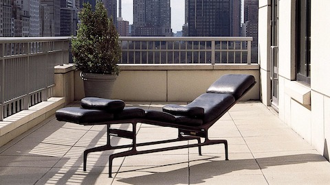 A black leather Eames Chaise situated on a balcony overlooking an urban skyline.