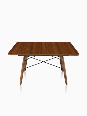 A square Eames Coffee Table with wood legs, metal cross-struts, and a medium wood top.