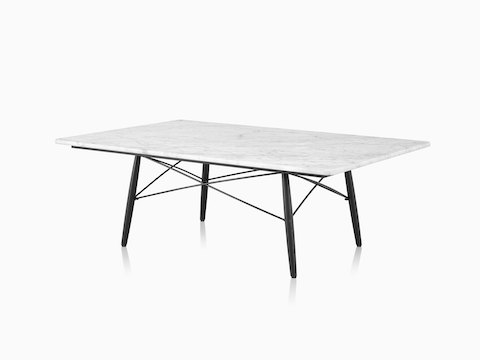 An angled view of a rectangular Eames Coffee Table with black wood legs, metal cross-struts, and a white marble top.