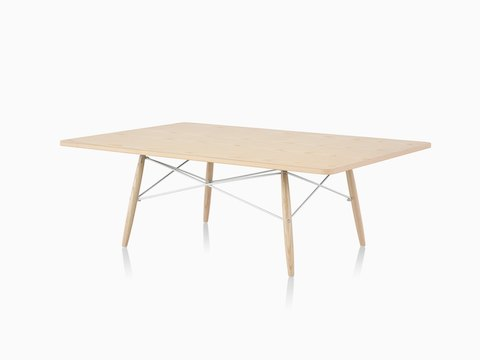 An angled view of a rectangular Eames Coffee Table with wood legs, metal cross-struts, and a light wood top.