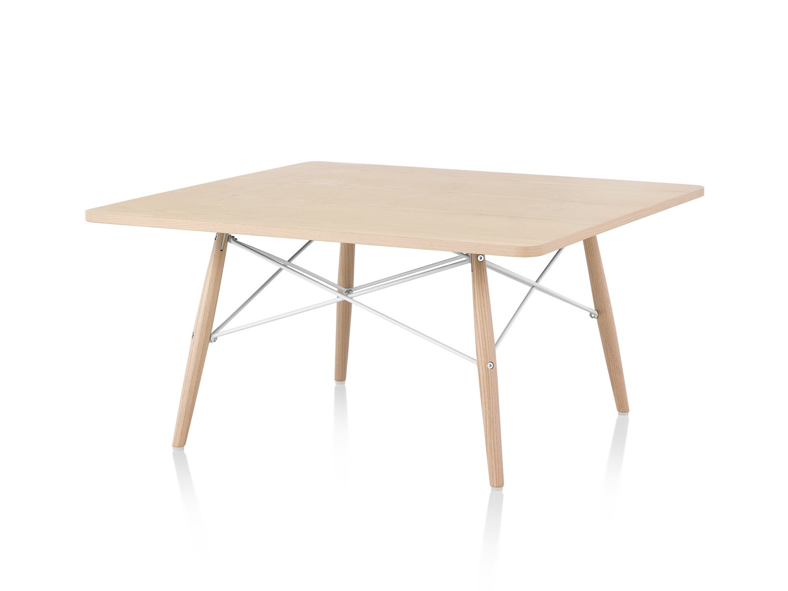 An angled view of an Eames Coffee Table with wood legs, metal cross-struts, and a light wood top.
