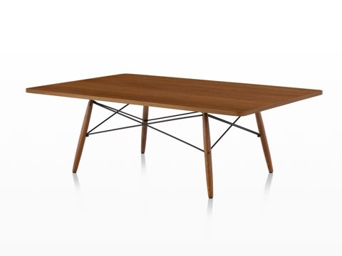 An angled view of a rectangular Eames Coffee Table with wood legs, metal cross-struts, and a medium wood top.