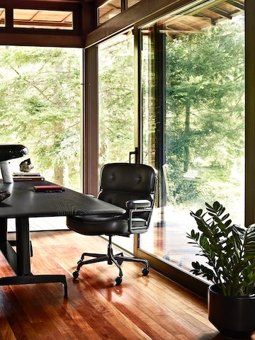 A black leather Eames Executive Chair with a black AGL table in a glass-walled home office overlooking trees.