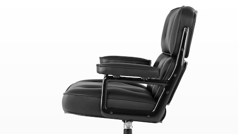 Profile view of a black leather Eames Executive Chair, showing the thickly cushioned seat, back, and arms.