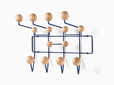 Angled view of an Eames Hang-It-All storage rack, featuring a black wire frame and wood knobs in a light finish.