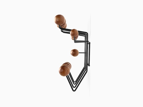 Profile view of an Eames Hang-It-All storage rack, featuring a black wire frame and wood knobs in a medium finish.