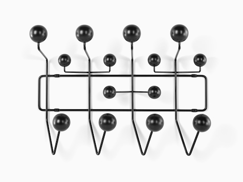 An Eames Hang-It-All storage rack, featuring a black wire frame and black wood knobs.