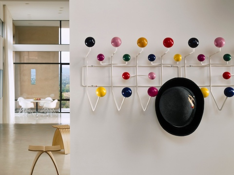A man's hat hangs from one of two adjacent Eames Hang-It-All storage racks, both with a white wire frame and multicolored knobs.