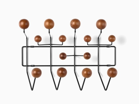 An Eames Hang-It-All storage rack, featuring a black wire frame and wood knobs in a medium finish.