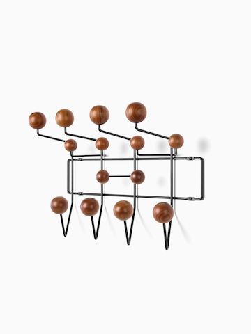 An Eames Hang-It-All storage rack with wood knobs. Select to go to the Eames Hang-It-All product page.