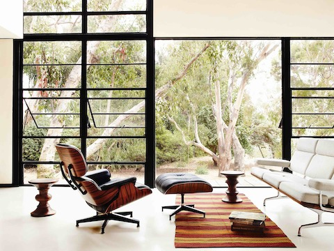 A black leather Eames Lounge Chair and Ottoman, Eames Sofa, and two Eames Walnut Stools near a glass wall.