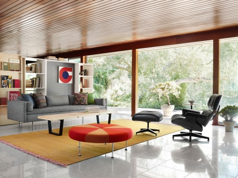 A black leather Eames Lounge Chair and Ottoman and a gray Bolster Sofa anchor a residential setting with an outdoor view.