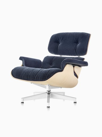An Eames Lounge Chair with blue mohair upholstery and a white ash veneer shell, viewed from a 45-degree angle.