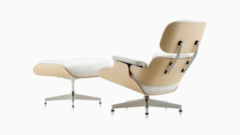 Three-quarter rear view of a white leather Eames Lounge Chair and Ottoman with a white ash veneer shell.