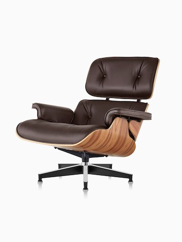 Brown Eames Lounge Chair With A Wood Veneer Shell, Viewed From A 45 Degree