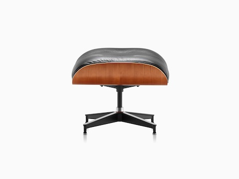 Black leather Eames Ottoman with a wood veneer shell, viewed from the side.
