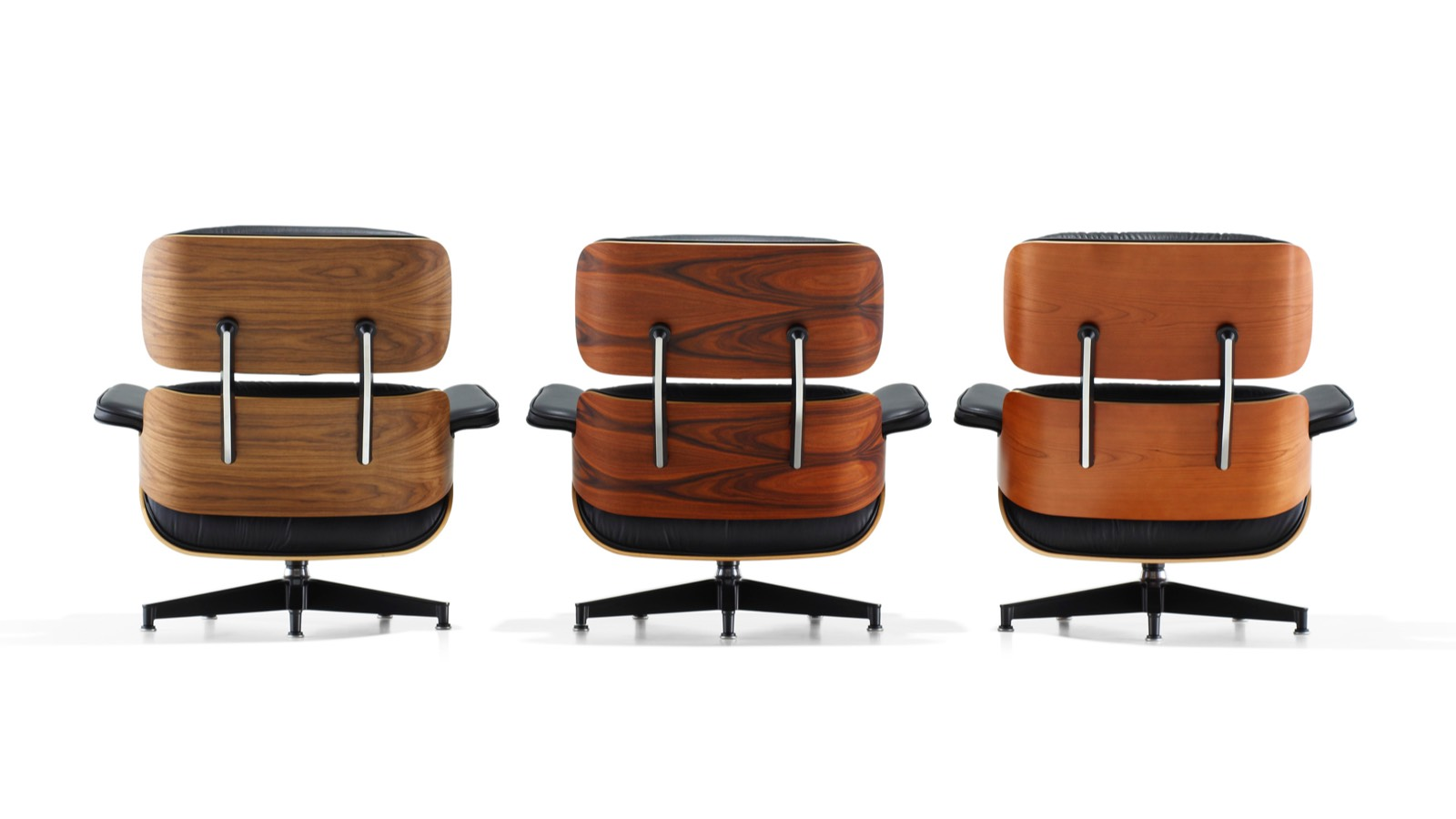 Three Eames Lounge Chairs, each with a different wood veneer finish, viewed from the rear.
