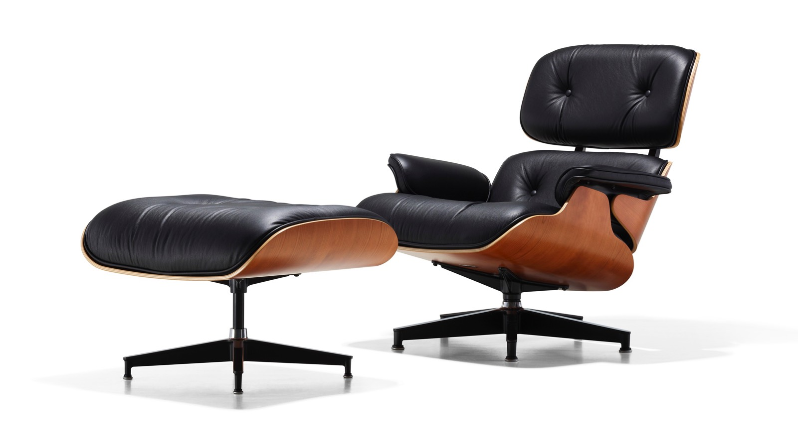 Black leather Eames Lounge Chair and Ottoman with a wood veneer shell, viewed from a 45-degree angle.