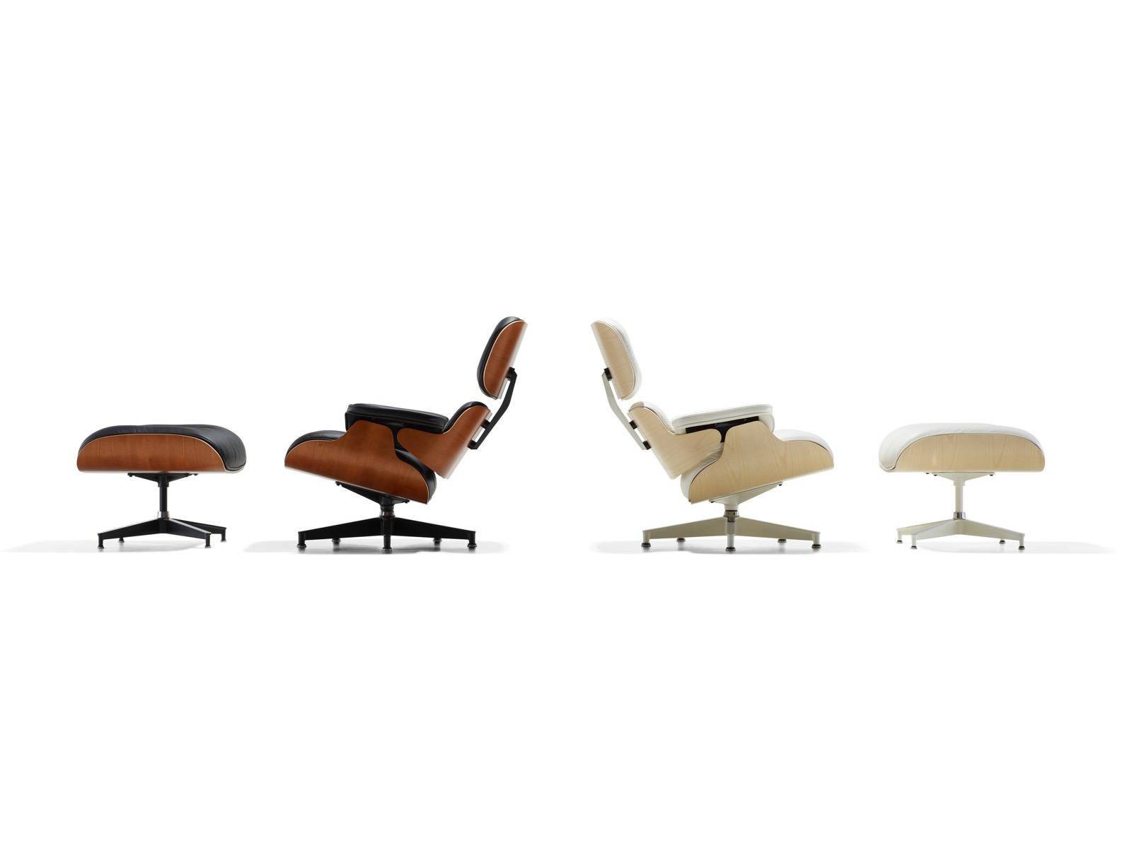A black leather Eames Lounge Chair and Ottoman and a white leather Eames Lounge Chair and Ottoman, positioned back to back.