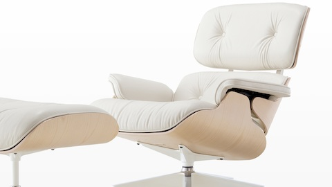White leather Eames Lounge Chair and Ottoman with a white ash veneer shell, viewed from a 45-degree angle.