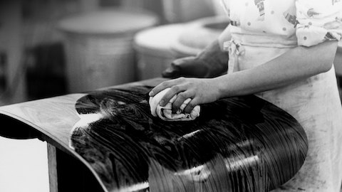 Close view of a hand applying the finish to the shell of an Eames Lounge Chair.