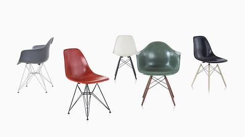 Several red Eames Molded Fiberglass side chairs with dowel legs around a conference table.