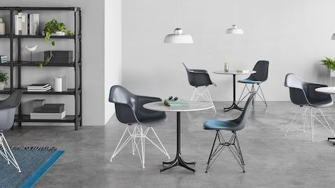 Casual work setting featuring Eames Molded Fiberglass stools in blue upholstery.