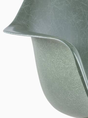 An up close view of the shell of a dark green Eames Molded Fiberglass Chair.