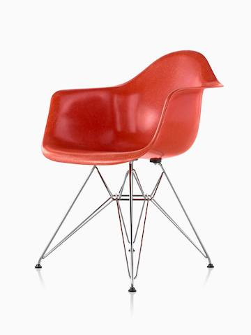 Red Eames Molded Fiberglass side chair with an upholstered seat pad and dowel legs, viewed from a 45-degree angle.