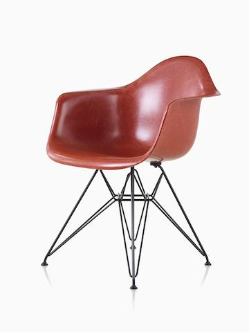 Black upholstered Eames Molded Fiberglass armchair with dowel legs, viewed from a 45-degree angle.