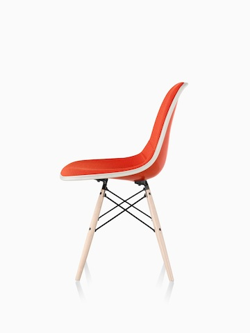 Red Eames Molded Fiberglass side chair with full upholstery and dowel legs, viewed from the side.